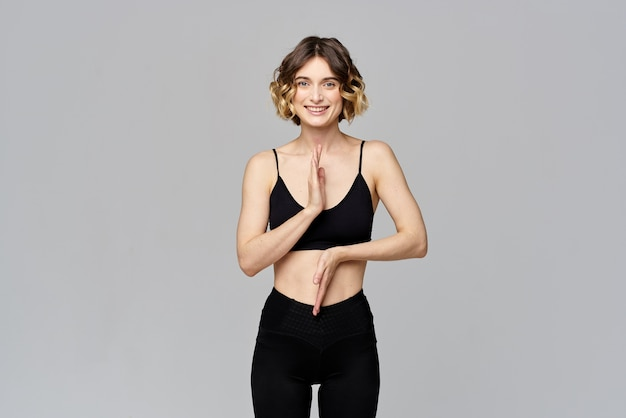 Une femme mince fait des gestes avec ses mains sur une figure grise sport fitness.