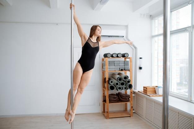 Femme mince sur la formation de pole-dance en classe. danseuses professionnelles exerçant dans la salle de gym, pole dance.