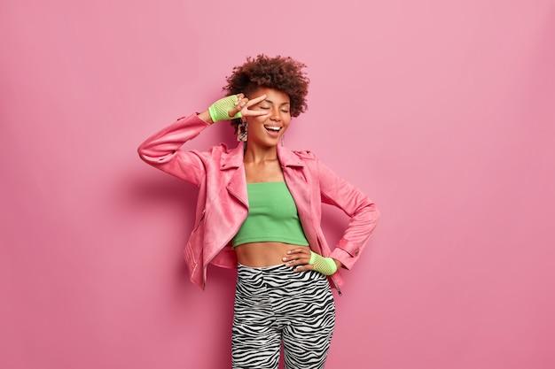 Femme mince insouciante aux cheveux afro fait un geste de paix garde la main sur la taille et se sent heureuse
