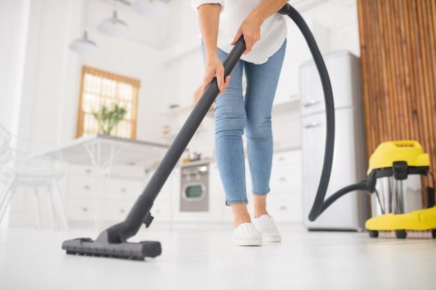 Femme mince en jeans et mocassins après-midi passer l'aspirateur dans la cuisine blanche