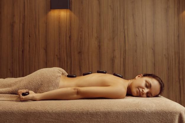 Femme mince avec des pierres sur le dos allongée sur une table de massage, vue latérale. massages et relaxation, soins du corps et de la peau. personne de sexe féminin relaxant dans un salon spa