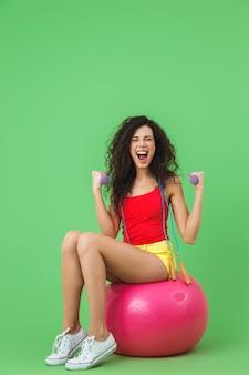 Femme mince portant des vêtements d'été soulevant des haltères alors qu'elle était assise sur un ballon de fitness pendant l'aérobic contre le mur vert