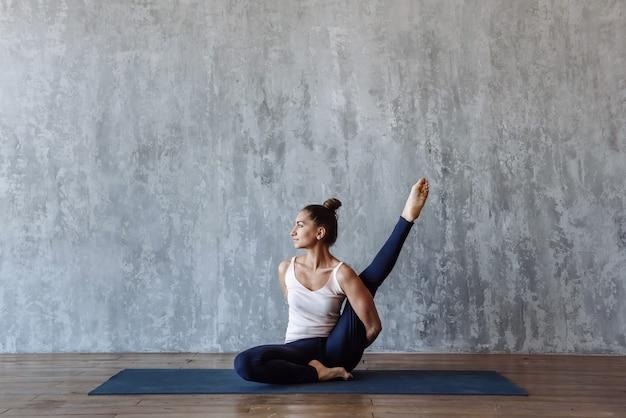 Femme mince pratiquant le yoga sur un tapis à l'intérieur, faisant des étirements de pilates dans une pose sur le sol