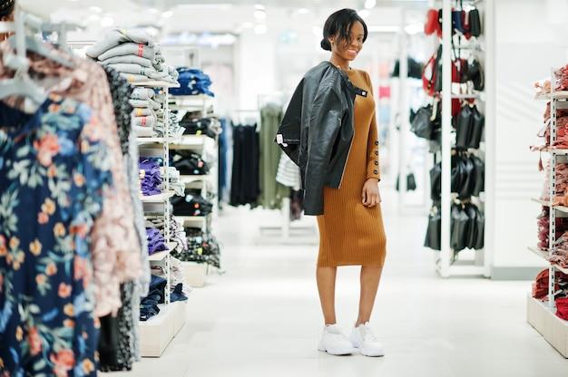Femme mince en robe tunique marron et veste en cuir noire