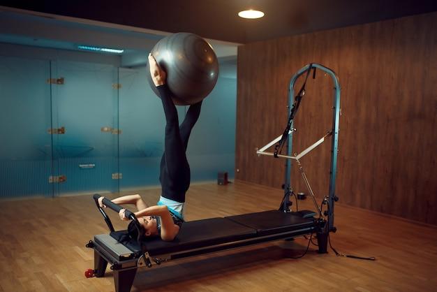 Femme mince en tenue de sport, formation de pilates avec ballon sur machine d'exercice dans la salle de gym. workuot de remise en forme dans un club de sport.