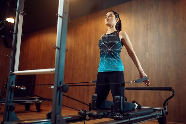 Femme mince en tenue de sport, formation de pilates sur machine d'exercice dans la salle de gym. workuot de remise en forme dans un club de sport.