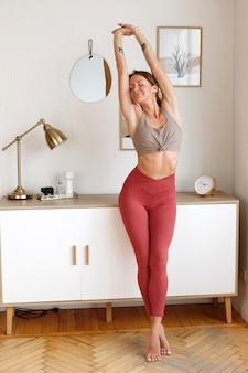 Femme mince en tenue de sport à la maison après une séance d'entraînement