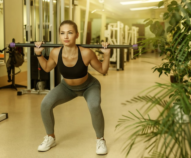 Une femme mince en vêtements de sport fait un exercice de squat avec une barre sur les épaules de la salle de sport. concept de mode de vie sain.