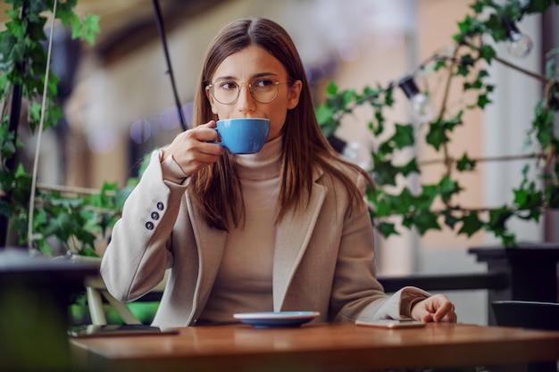 Femme à la mode assise à la cafétéria et appréciant son café préféré