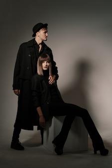Femme à la mode assise sur un cube tandis que l'homme debout derrière elle