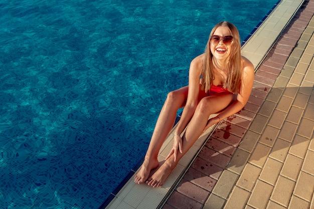 Femme à la mode en bikini rouge assis près de la piscine
