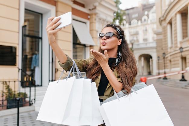 Femme à la mode bronzée faisant selfie avec l'expression du visage embrassant après le shopping