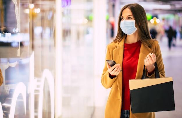 Femme à la mode confiante dans un masque médical de sécurité avec un sac à provisions et un téléphone intelligent se promène dans le centre commercial