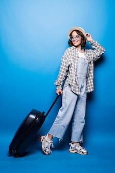 Femme à la mode en cours d'exécution avec valise