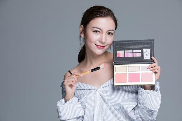 Femme à la mode dans une chemise tenant une palette de maquillage