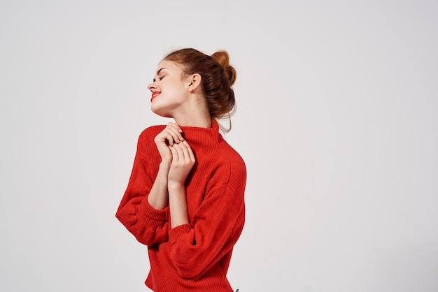 Femme à la mode dans un fond clair de pull rouge. photo de haute qualité