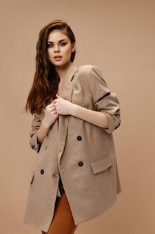 Femme à la mode dans un manteau et porte-clés faisant des gestes avec ses mains sur fond beige