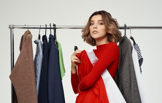 Femme à la mode dans un pull rouge se tient près d'une armoire avec des vêtements de chemise. photo de haute qualité