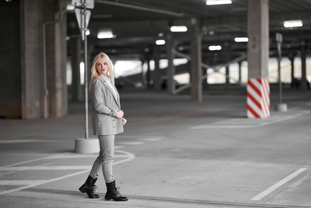 Femme à la mode dans une veste posant dans le parking