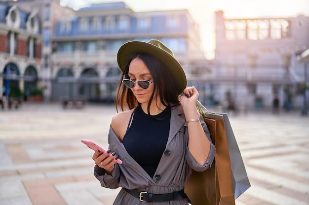Femme à la mode élégante jeune hipster shopaholic avec des sacs en papier à l'aide de téléphone