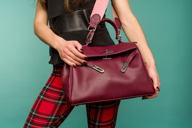 Femme à la mode élégante portant des pantalons à carreaux tenant un sac à main sac de couleur bordeaux