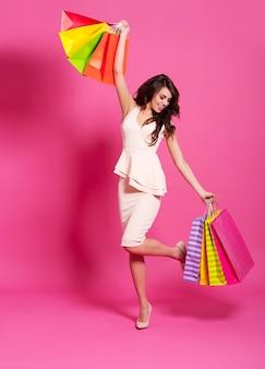 Femme de mode excitée avec des sacs à provisions