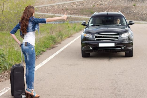 Femme à la mode faisant de l'auto-stop sur une route de campagne