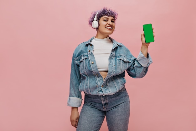 Femme à la mode en haut blanc et costume de jeans tient le téléphone dans ses mains et sourit. jolie femme au casque et aux cheveux violets