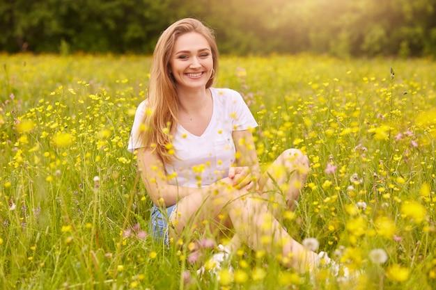 Femme de mode jeune posant dans la prairie d'été. fille branchée au paysage naturel