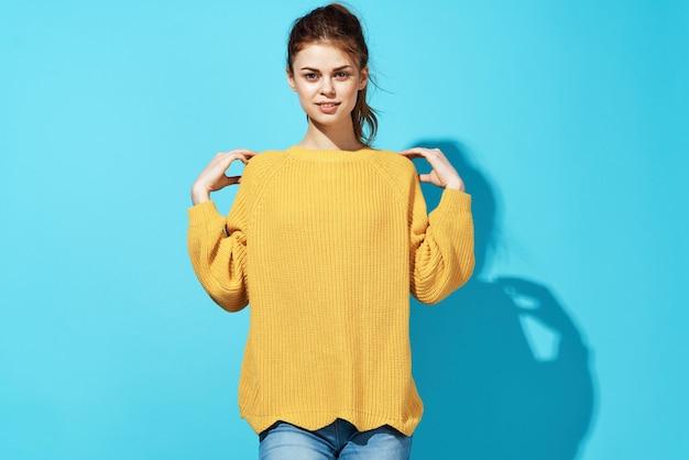 Femme à la mode joyeuse en pull jaune posant fond bleu de vêtements de mode