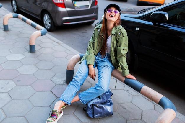 Femme à la mode avec de longs poils bruns posant à l'extérieur dans une grande ville près de la route