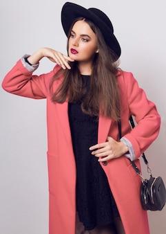 Femme à la mode en manteau rose et chapeau noir posant