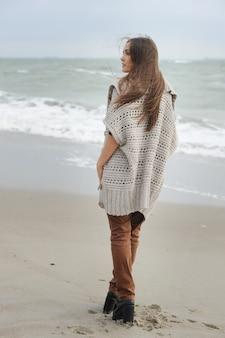 Femme de mode marchant seule sur une plage de la mer, tissu oversize décontracté, automne en plein air