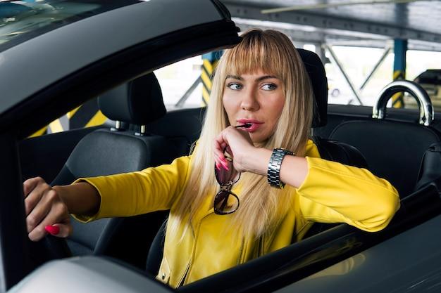 Femme à la mode mordant ses lunettes avec une expression réfléchie sur son visage. fille blonde à lunettes de soleil au volant d'une voiture décapotable