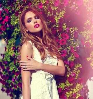 Femme à la mode posant devant des fleurs
