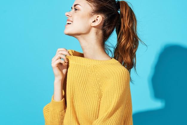 Femme en mode pull jaune posant glamour gros plan