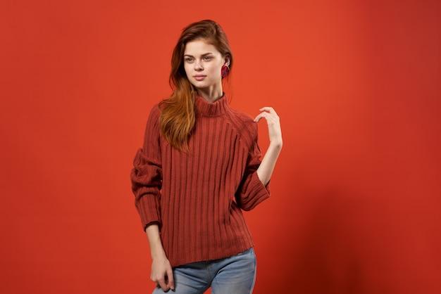 Femme à la mode en pull rouge et jeans vêtements décontractés posant fond isolé.
