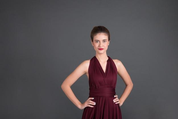 Femme de mode qui pose en robe violette sexy, maquillage de mode, look de luxe.