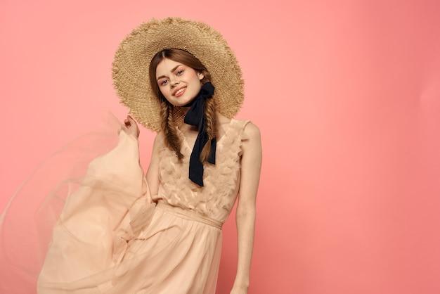 Femme à la mode en robe et chapeau avec ruban noir sur la vue recadrée rose du plaisir des émotions du modèle.