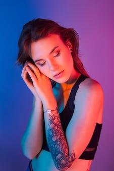 Femme à la mode de style rétro posant dans des lumières bleues et roses pourpres