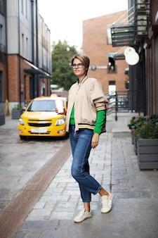 Femme de mode de style de rue portant des vêtements à la mode buvant du café en attente de la tendance de la tenue de taxi