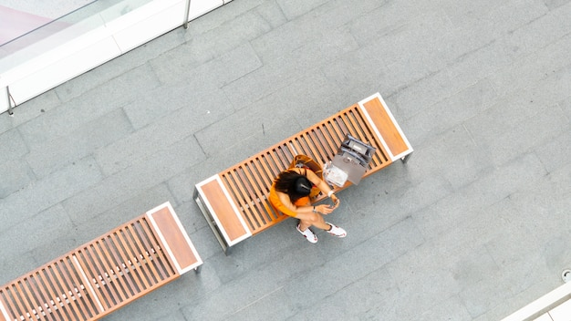Femme de mode supérieure vue aérienne avec sac à provisions utilise un smartphone assis sur un banc en bois au passage couvert pour piétons avec flou personnes marchent