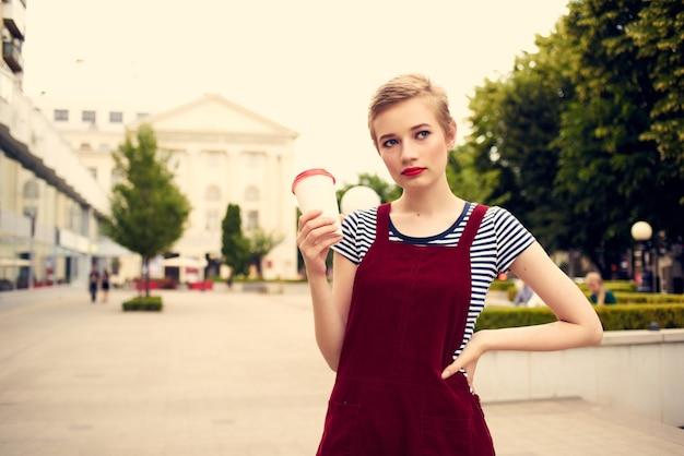 Femme à la mode avec une tasse de café à l'extérieur à l'extérieur