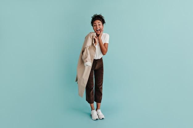 Femme à la mode tenant un trench-coat
