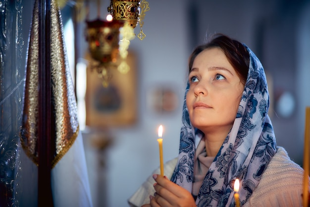 Femme de mode de vie allume des bougies dans l'église, priant devant l'icône
