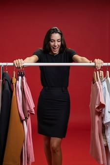 Femme de mode vue de face à la recherche de nouveaux vêtements