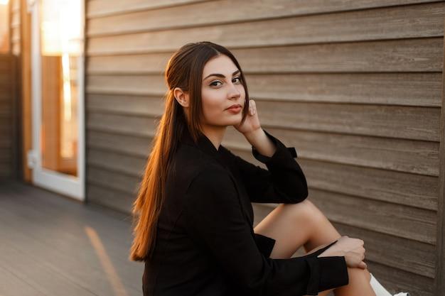Femme modèle assez élégante dans un manteau élégant noir se trouve près d'un mur en bois au coucher du soleil