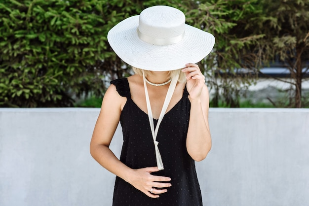 Femme modèle dans une robe noire dans un beau chapeau posant dans une nouvelle collection de catalogue de chapeaux