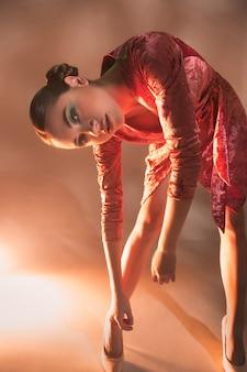 Femme modèle haute couture dans des lumières vives colorées qui pose en studio,