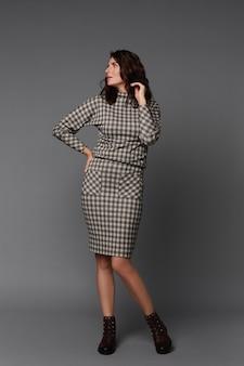 Femme modèle intermédiaire avec une grande silhouette vêtue d'une robe à carreaux sur la surface grise